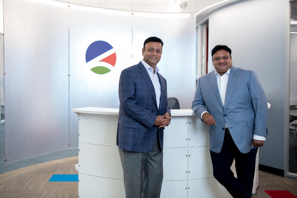 Vikash and Vikram Agrawal standing in front of a desk, with the Levrx logo pictured behind them.