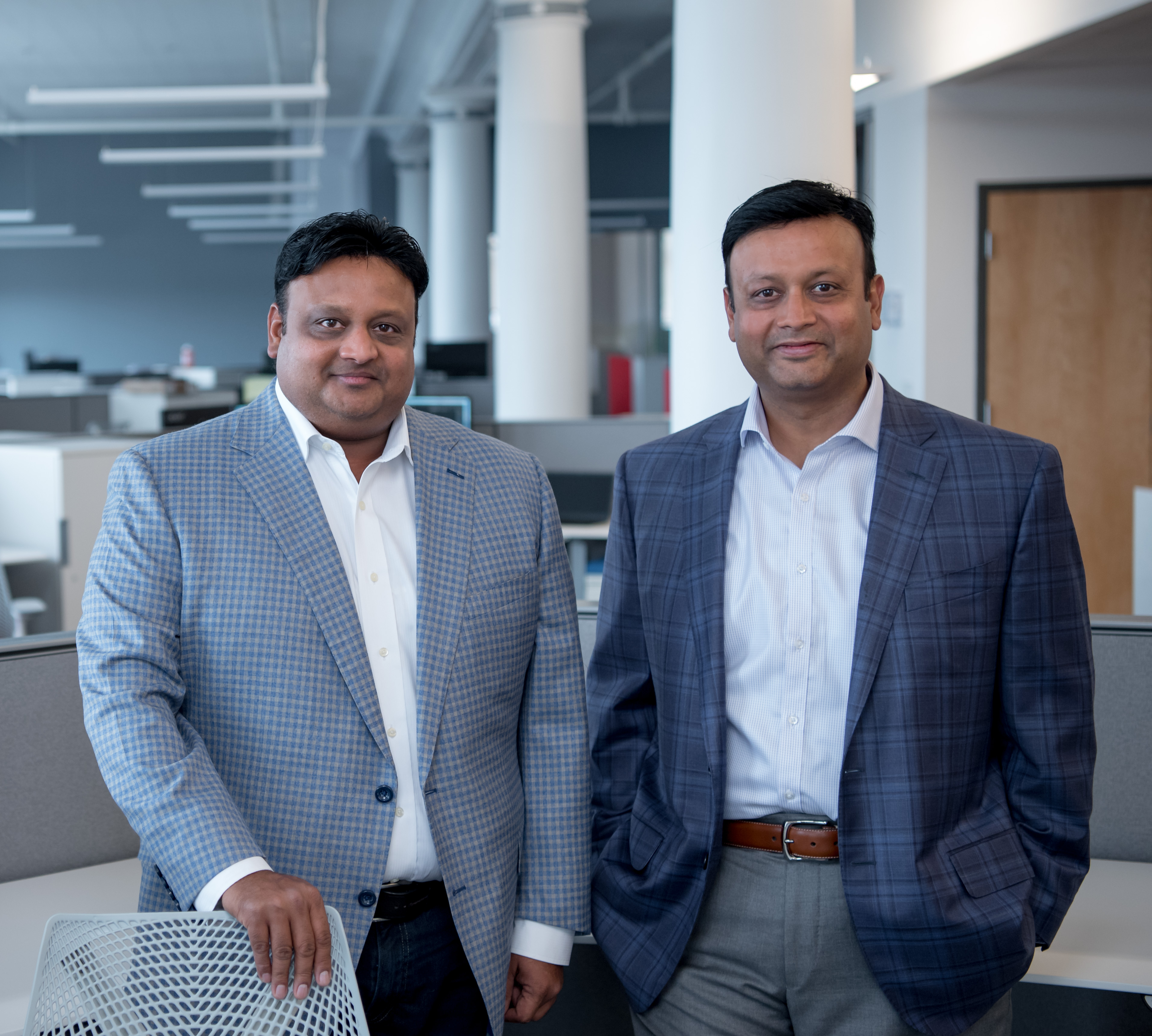 Pictured are two men in an office. Pictured left is Vikram Agrawal and right is Vikash Agrawal.